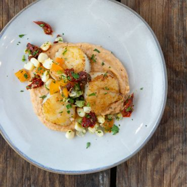 Seared Sea Scallops atop hummus with Corn Relish